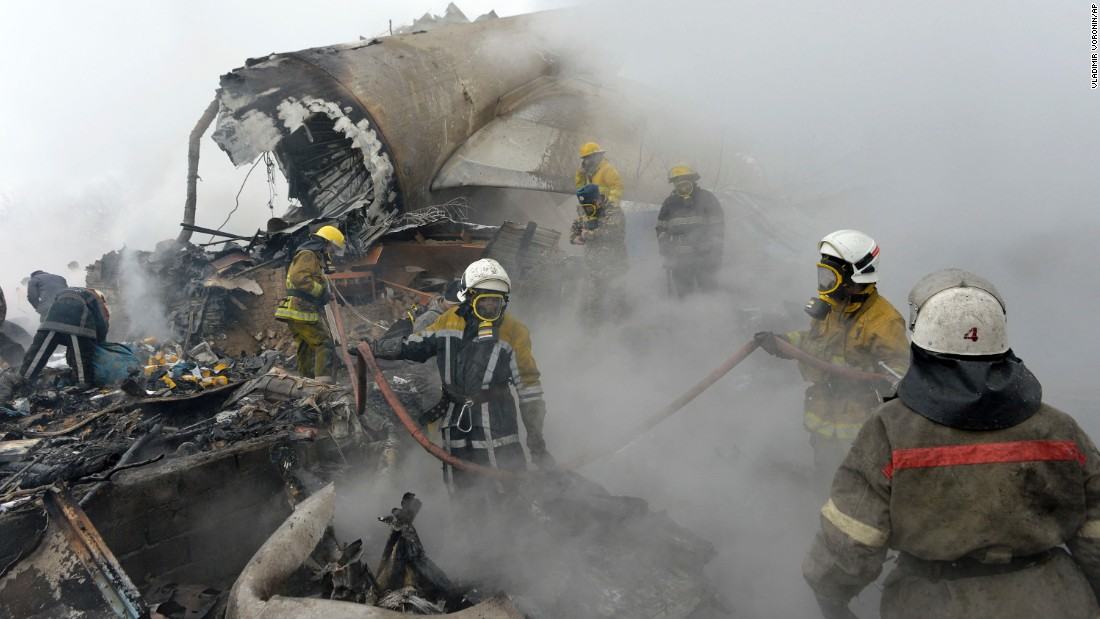 Kyrgyz firefighters work in the wreckage of the plane.