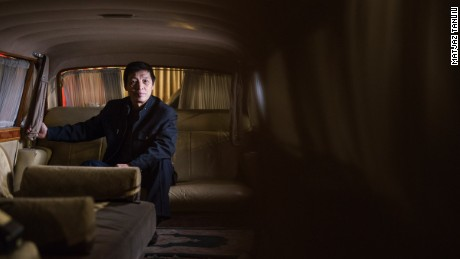 Luo Wenyou poses inside a stretch limo manufactured by Hongqi. It was intended for Mao Zedong.