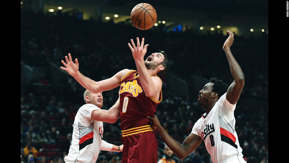 Cleveland Cavaliers forward Kevin Love battles for a rebound with Portland Trail Blazers center Mason Plumlee, left, and forward Al-Farouq Aminu in the first half of an NBA basketball game on January 11 in Portland, Oregon.