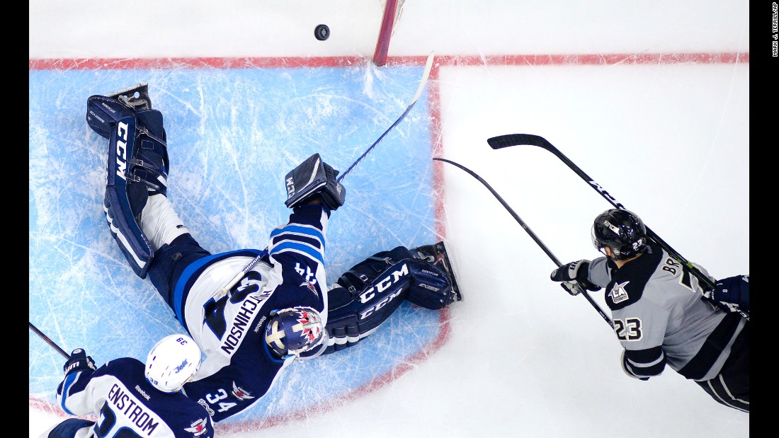 Los Angeles Kings' Dustin Brown, right, scores on Winnipeg Jets goalie Michael Hutchinson during the third period of an NHL hockey game on Saturday, January 14. The Kings won 3-2 in overtime.
