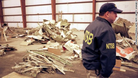 A National Transportation Safety Board Official stands with piles of wreckage from EgyptAir Flight 990 on November 1, 2000.