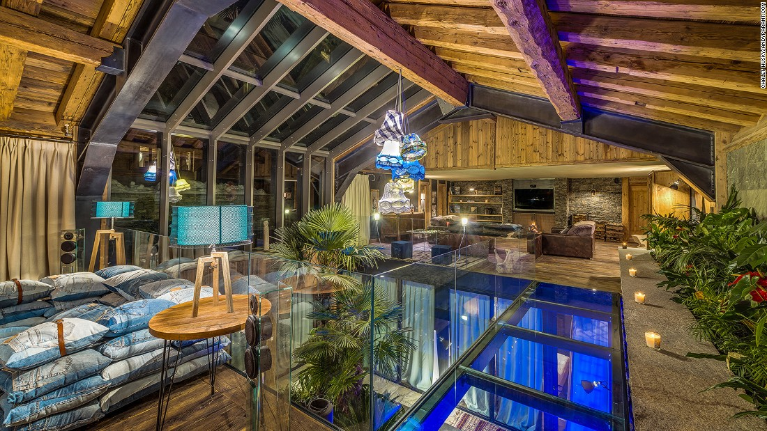 <strong>Chalet Husky, Val d'Isere (France):</strong> Chalet Husky features a vast open-plan living space. Its bar and dining area is linked with a sofa-surrounded open fireplace by a glass walkway over an indoor atrium garden.