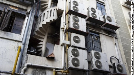 Air conditioning units line a side of a building in downtown New Delhi.