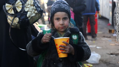 A Syrian girl evacuated from the last rebel-held pockets of Syria's northen city of Aleppo, eats upon arriving in the opposition-controlled Khan al-Assal region on December 20, 2016.