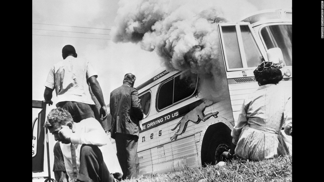 Freedom Riders sit outside a bus after it was set on fire by a white mob in Anniston on May 14, 1961.