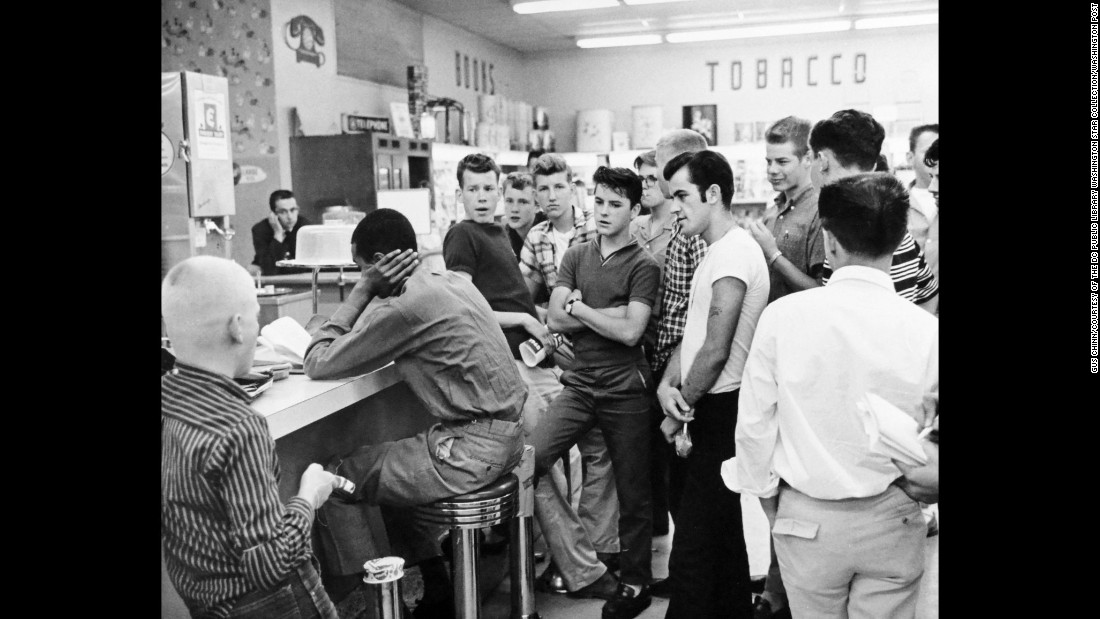 Dion Diamond is harassed during a sit-in at the Cherrydale Drug Fair in Arlington, Virginia. He was part of a small group called the Non-Violent Action Group. Some people threw lit cigarettes at group members, while others kicked them. The two-week protests in June 1960 led to the integration of restaurants in Arlington. Restaurants soon followed in nearby Alexandria and Fairfax.