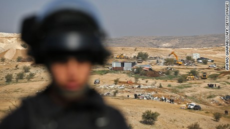An Israeli officer on guard as bulldozers demolish homes in the Bedouin village of Umm al-Hiran.