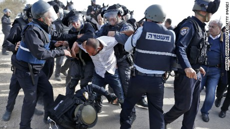 Israeli policemen clash with a Bedouin man following a protest in the Negev Desert on Wednesday.