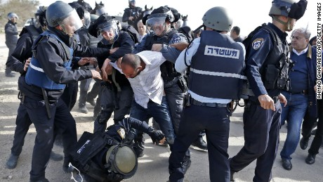 Israeli policemen clash with a Bedouin man following a protest against home demolitions on January 18, 2017 in the Bedouin village of Umm al-Hiran, which is not recognized by the Israeli government, near the southern city of Beersheba, in the Negev desert.