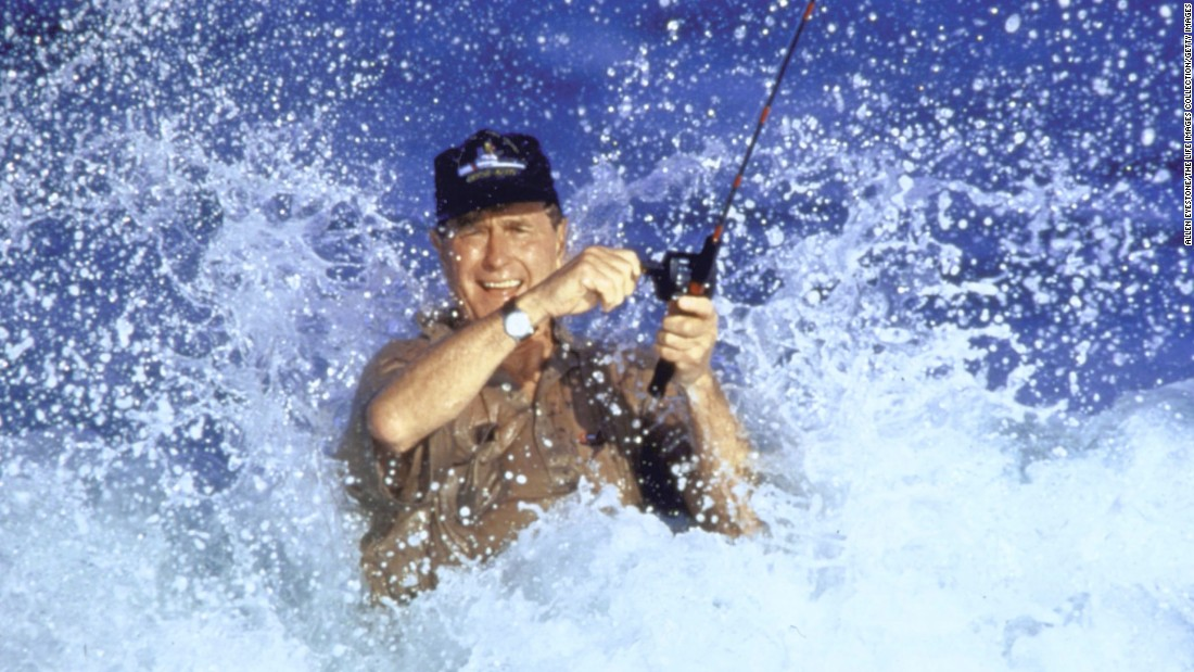 Bush fights a wave as he casts a fishing line in Florida in 1988.