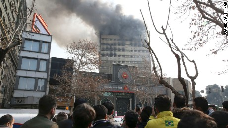 Iranians watch the Plasco building where smoke rises from its windows in central Tehran, Iran, Thursday, Jan. 19, 2017. The high-rise building engulfed by a fire collapsed on Thursday as scores of firefighters battled the blaze. (AP Photo/Vahid Salemi)