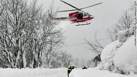 epa05729936 A handout picture provided by rescuers shows a helicopter and rescue workers en route to hotel Rigopiano after it was hit by an avalanche in Farindola (Pescara), Abruzzo region, early 19 January 2017. According to an Italian mountain rescue team, several people have been killed in an avalanche that has hit a hotel near the Gran Sasso mountain in Abruzzo region. Authorities believe that the avalanche was apparently triggered by a series of earthquakes in central Italy on 18 January.  EPA/ITALIAN MOUNTAIN RESCUE HANDOUT BEST QUALITY AVAILABLE HANDOUT EDITORIAL USE ONLY/NO SALES