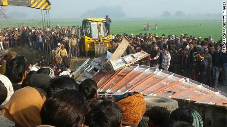 Indian bystanders gather near the scene of a bus crash in Etah in the state of Uttar Pradesh on January 19, 2017.  At least 15 children were killed and dozens more injured when a school bus collided with a truck in northern India on January 19, police said. The driver of the bus also died in the crash, the latest deadly accident in a country with one of the worst road safety records in the world.  / AFP / STR        (Photo credit should read STR/AFP/Getty Images)