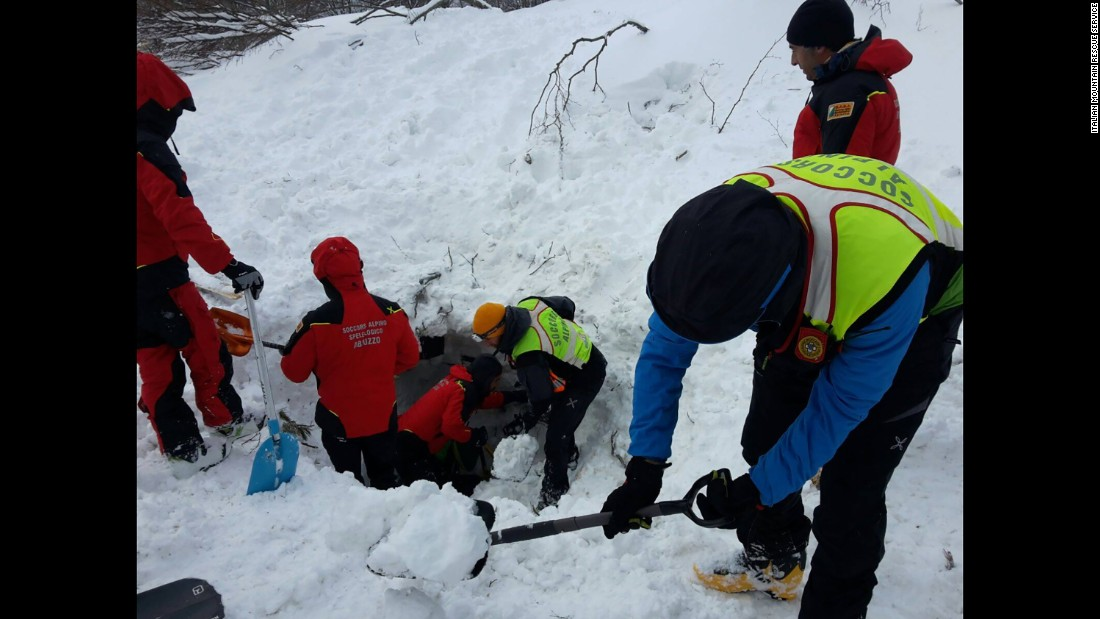 Rescuers dig for avalanche survivors after skiing several kilometers through blizzard conditions to reach the hotel.
