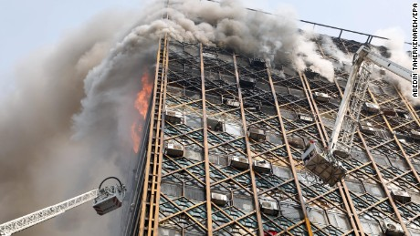 epa05730000 Iranian firefighters attempt to control fire at the Plasco building in Tehran, Iran, 19 January 2017. Iran's state-run Press TV reports that people are believed to be trapped inside the rubble. At least firefighters are believed to have died after being trapped on the upper floors of the building.  EPA/ABEDIN TAHERKENAREH