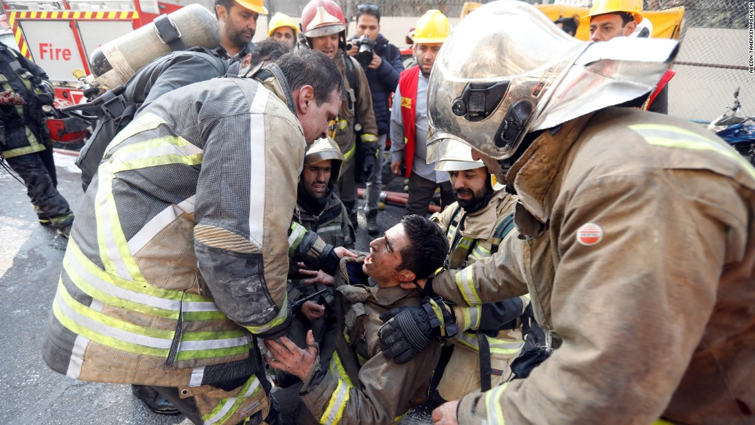 Iranian firefighters comfort a fellow fireman in the aftermath of the building collapse.