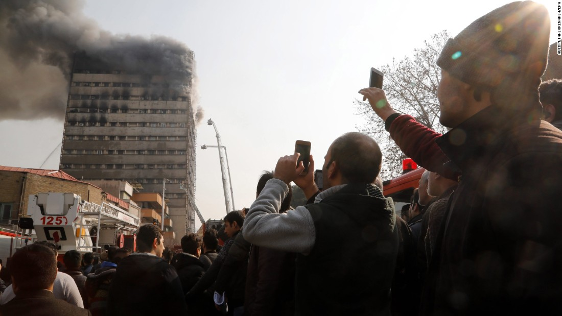 Residents take photos of the Plasco building engulfed in smoke and flames.