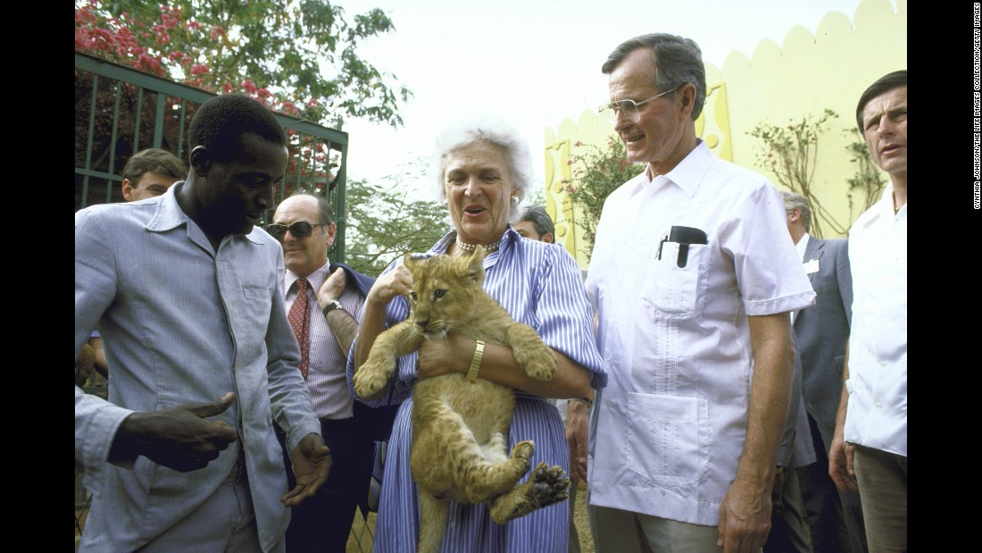 Barbara Bush holds a lion cub while she and her husband visit a garden project.