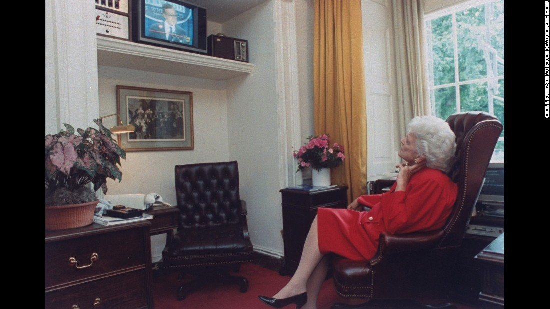 Bush watches her husband from a White House television as he speaks during a press conference. She served as first lady of the United States from January 1989-1993.
