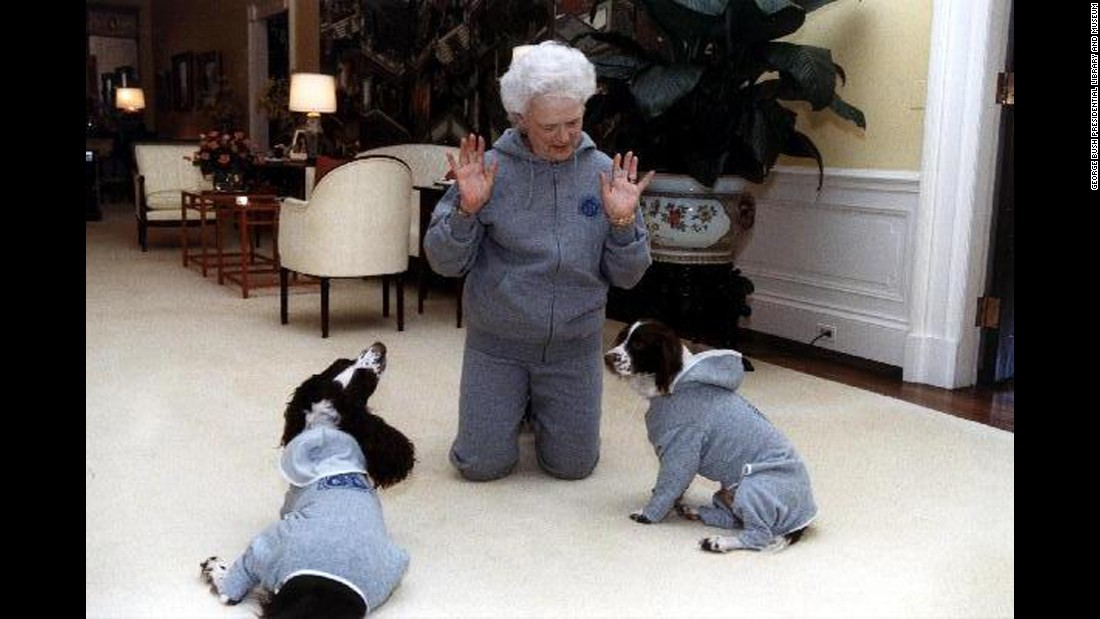 Bush and her dogs, Ranger and Millie, wear matching gray sweatsuits in the residence of the White House in Washington on January 9, 1991.