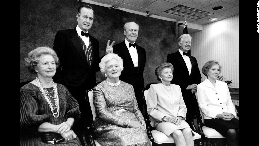 Bush's husband makes the peace sign with his hands during an event at the Gerald R. Ford Library in Grand Rapids, Michigan, on April 16, 1997. Also pictured are former Presidents Ford and Jimmy Carter, as well as former first ladies Lady Bird Johnson, Betty Ford and Rosalynn Carter.