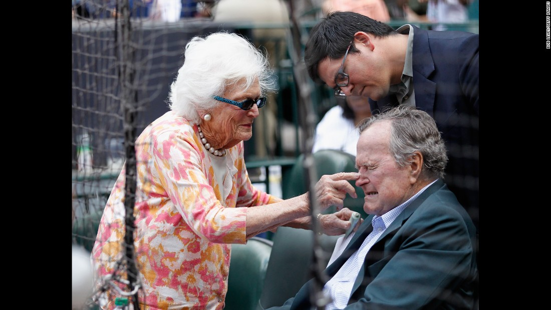 Barbara Bush puts some sunscreen on her husband's nose as they get ready to watch the Seattle Mariners play the Houston Astros in a Major League Baseball game in Houston, Texas, on May 3, 2015.