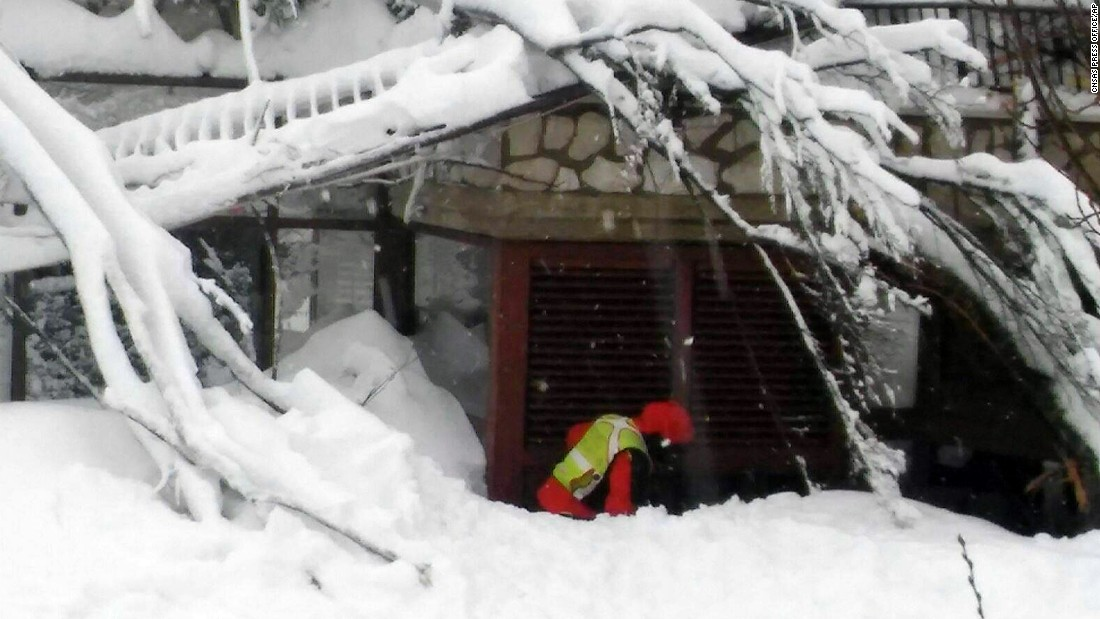 A rescuer clears snow in front of the hotel.