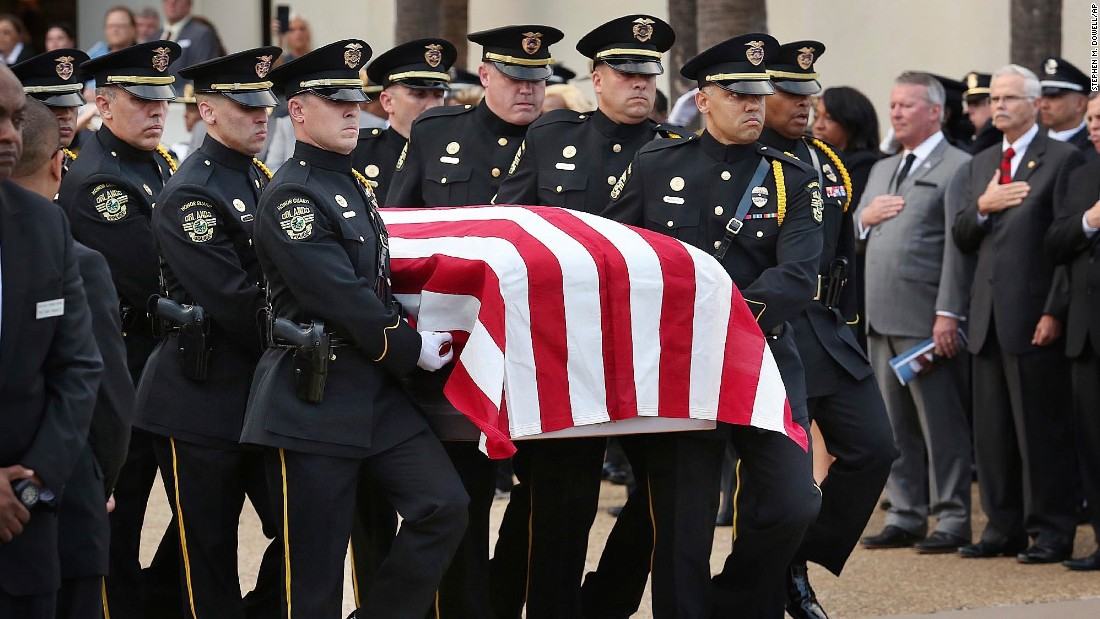 "The flag-draped casket of Orlando Master Sgt. Debra Clayton is carried to a hearse during her funeral at the First Baptist Church in Orlando on Saturday, January 14. Clayton, 42, <a href=""http://www.cnn.com/2017/01/13/us/beyond-the-call-of-duty-orlando/"" target=""_blank"">died after she was shot outside a Walmart</a> on January 9 by a suspect on the run. She was one of two officers Orlando lost that day."