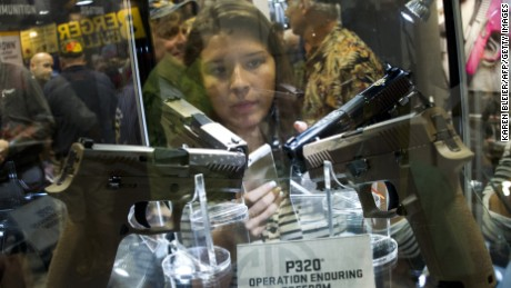 A girl looks at Sig Sauer P320 handguns April 11, 2015 at the 2015 NRA Annual Convention in Nashville, Tennessee.