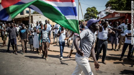 "A man waves a Gambian flag while he celebrates the victory of Gambia's opposition candidate Adama Barrow during the Presidential Elections on December 2, 2016, in Serekunda, Banjul. The impoverished west African nation of Gambia is set for a rare handover of power after long-serving President Yahya Jammeh suffered a shock defeat at the polls. Rights bodies and media watchdogs accuse Jammeh of cultivating a ""pervasive climate of fear"" during his 22 years in office and of crushing dissent against his regime.  / AFP / MARCO LONGARI        (Photo credit should read MARCO LONGARI/AFP/Getty Images)"