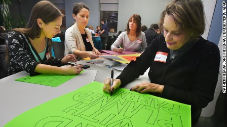 In this Thursday, Jan. 12, 2017, photo, Milford resident Ann Carter, right, and members of the Connecticut chapter of the National Organization for Women make signs before a meeting at the New Haven Free Public Library in New Haven, Conn. They were preparing for the Women's March on Washington on Saturday in Washington, D.C. The mission of Connecticut NOW is to ratify the equal rights amendment, protect women's reproductive freedom and abused girls. (Catherine Avalone/New Haven Register via AP)