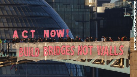 Activists from the Bridges not Walls movement display messages on Tower Bridge in London on January 20, 2017 to coincide with the inauguration of Donald Trump as the 45th president of the United States.  Trump will be sworn in as the 45th president of the United States on January 20 -- capping his improbable journey to the White House and beginning a four-year term that promises to shake up Washington and the world. The Bridges not Walls movement dropped banners with themed messages from London bridges across the Thames as an act of defiance against Trump's inauguration and to amplify their message against what they say is a rise of new far right politics in western democracies. / AFP / Daniel LEAL-OLIVAS        (Photo credit should read DANIEL LEAL-OLIVAS/AFP/Getty Images)