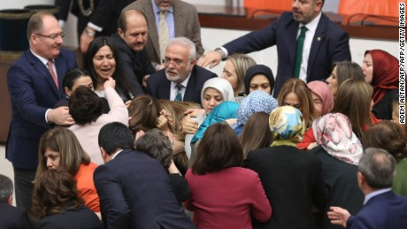 "Ruling AK Party and opposition lawmakers scuffle after Turkish deputy Aylin Nazliaka had handcuffed herself to the podium in a protest against the constitutional reform aimed at strengthening the powers of the Turkish president during a debate at the Turkish Parliament in Ankara on January 19, 2017. The proposed changes which will create an executive presidency for the first time in modern Turkey, are controversial and far-reaching, with Human Rights Watch (HRW) claiming they would ""weaken parliamentary oversight of the executive"". / AFP / Adem ALTAN        (Photo credit should read ADEM ALTAN/AFP/Getty Images)"