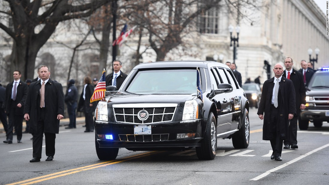 Secret Service members surround the presidential limousine as it drives up Pennsylvania Avenue during the Presidential Inaugural Parade on Friday, January 20, in Washington.