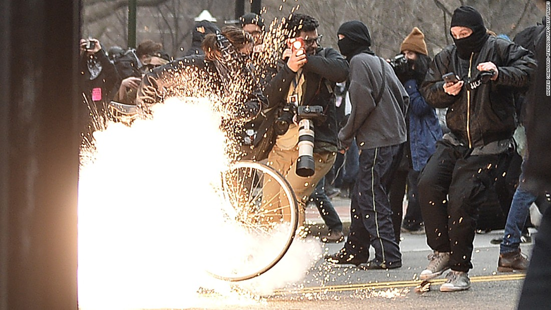 "A police flash-bang grenade explodes during a clash with protesters. ""Pepper spray and other control devices were used to control the criminal actors and protect persons and property,"" police said."