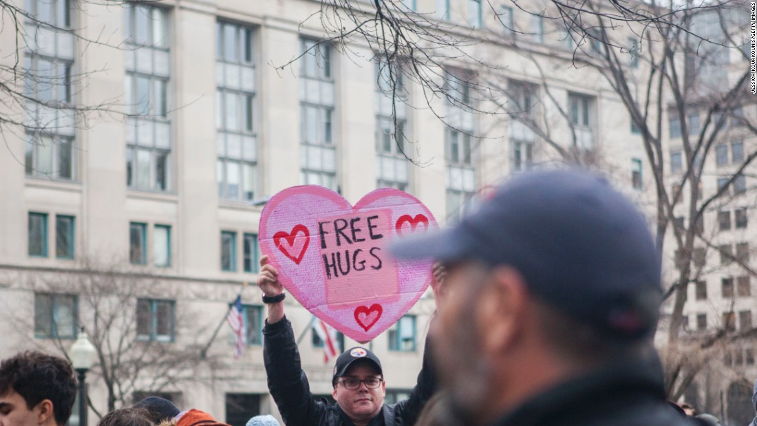 A man holds a sign offering free hugs during the protests.