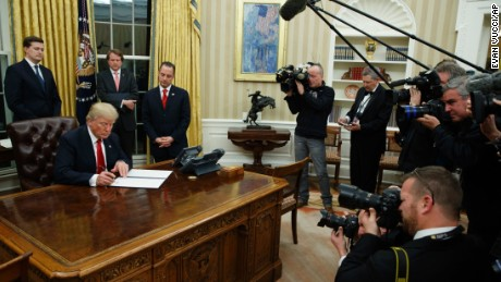 President Donald Trump signs his first executive order in the Oval Office of the White House on January 20, 2017.
