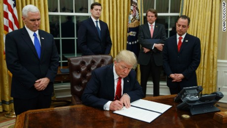 President Donald Trump, flanked by Vice President Mike Pence and Chief of Staff Reince Priebus, signs his first executive order on health care, Friday, Jan, 20, 2017, in the Oval Office of the White House in Washington. (AP Photo/Evan Vucci)