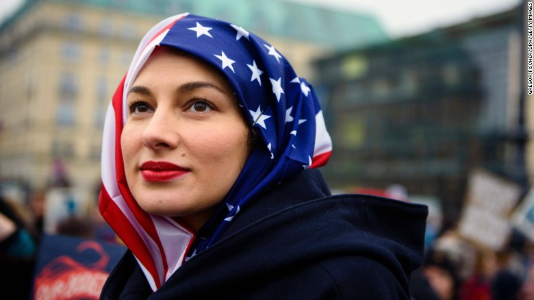 A woman wears a US flag like a hijab during a protest of US Democrats Abroad in front of the Brandenburg Gate in Berlin on January 21, 2017, one day after the inauguration of the US President.