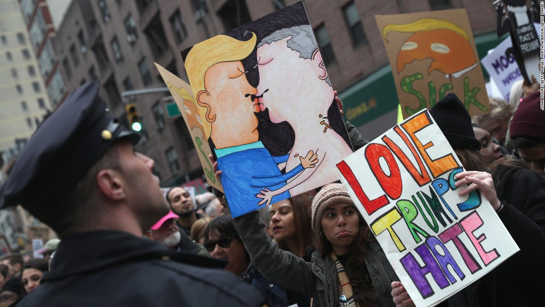 People hold up a drawing of Donald Trump and Vladimir Putin kissing while taking  of part in the Women's March on January 21, 2017 in New York City. The Midtown Manhattan event was one of many anti-Trump protests nationwide that came a day after Donald Trump was sworn in as the 45th President of the United States.