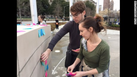 Dylan Stone-Miller and his girlfriend, Andrea McGrath, stand at a wall near the Georgia state Capitol.