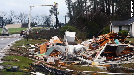 "The remains of a house sit in a debris pile along Highway 122 as power line workers repair a downed line Sunday, January 22, 2017, near Barney, Georgia. The National Weather Service said Sunday that southern Georgia, northern Florida and the corner of southeastern Alabama could face ""intense and long track"" tornadoes, scattered damaging winds and large hail."