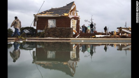 People are reflected in a swimming pool as they work to clean up at a home that was damaged by a tornado, Sunday, January 22, 2017, in Adel, Georgia. Gov. Nathan Deal declared a state of emergency in several counties, including Cook, that have suffered deaths, injuries and severe damage from weekend storms.