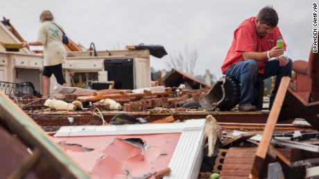 Jeff Bullard sits in what used to be the foyer of his home as his daughter, Jenny Bullard, looks through debris at their home that was damaged by a tornado, Sunday, January 22, 2017, in Adel, Georgia Gov. Nathan Deal declared a state of emergency in several counties, including Cook, that have suffered deaths, injuries and severe damage from weekend storms.