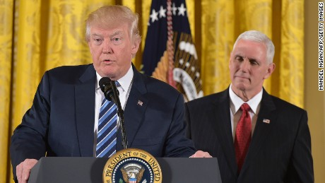 President Donald Trump speaks, as Vice President Mike Pence watches, before the swearing in of the White House senior staff at the White House on January 22, 2017, in Washington, DC.