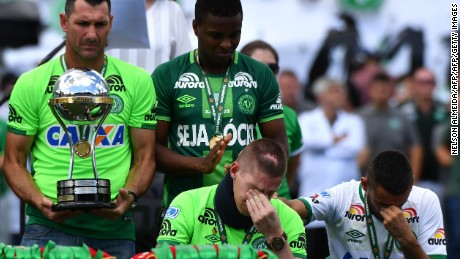 Brazilian Chapecoense footballers Alan Ruschel (R) and Jackson Follmann (C), survivors of the LaMia airplane crash in Colombia, receive the Copa Sudamericana trophy at the Arena Conda stadium in Chapeco, Santa Catarina state, in southern Brazil on January 21, 2017, before a friendly match against Palmeiras - Brazilian Champion 2016.  Most of the members of the Chapocoense football team perished in a November 28, 2016 plane crash in Colombia. / AFP / NELSON ALMEIDA        (Photo credit should read NELSON ALMEIDA/AFP/Getty Images)