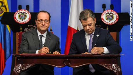 Colombian President Juan Manuel Santos (R) and French President Francois Hollande sign agreements at Narino Palace in Bogota on January 23, 2017. Hollande is on a Latin American tour to Chile and Colombia -- one of his last foreign trips before stepping down after April-May elections choose his successor. / AFP / Luis ACOSTA        (Photo credit should read LUIS ACOSTA/AFP/Getty Images)
