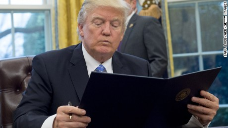 President Donald Trump reads an executive order withdrawing the US from the Trans-Pacific Partnership prior to signing it in the Oval Office of the White House in Washington, DC, January 23, 2017.