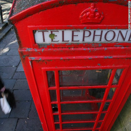 BATH, UNITED KINGDOM - FEBRUARY 06: A woman walks past a traditional red telephone box in a street in Bath on February 6, 2008 in Somerset, United Kingdom. According to BT payphone use in the UK has halved in three years, mainly due to the increased ownership of mobile phones. The iconic K6 telephone kiosk was designed in the 1930s and has become a much loved piece of British street furniture, however with with ever decreasing use, their long term future is under threat. (Photo by Matt Cardy/Getty Images)