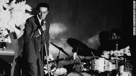 American comedian Lenny Bruce (1926 - 1966) performs on stage with exotic dancer Windee Gayle and a saxophonist at the Orchid Room, Waikiki, 1950s. (Photo by Hulton Archive/Getty Images)